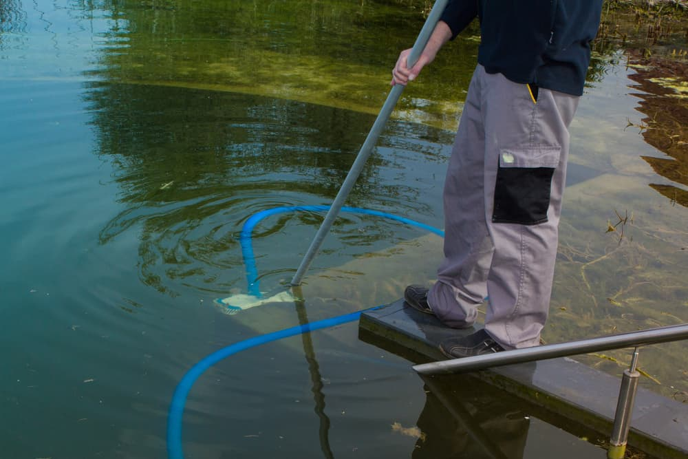 Person vacuuming the bottom of a dirty pond
