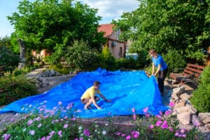 two people laying out a blue pond liner